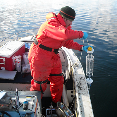 Man takes water sample from boat