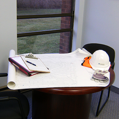 hard hat and work plans on table