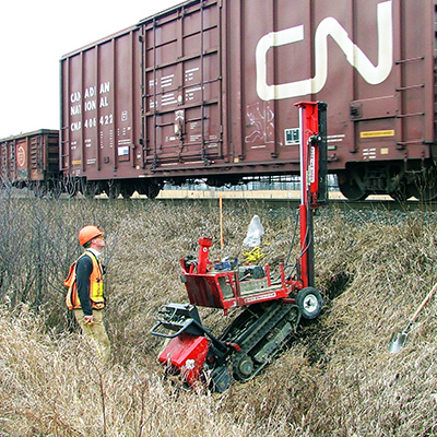 man takes environmental samples from ditch beside train