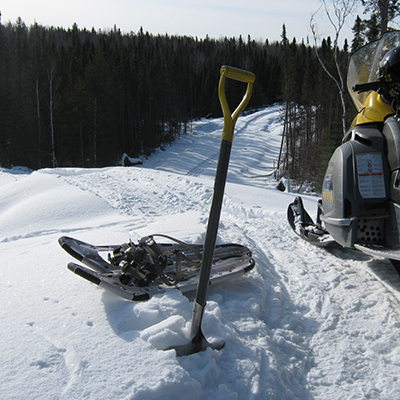 snowmobile, snowshoes, and shovel in the snowy wilderness