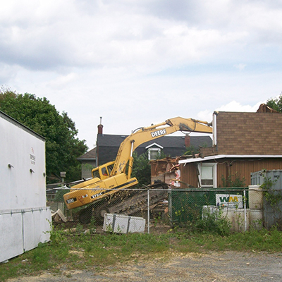 house being taken down with an excovator