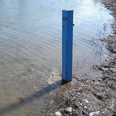 blue post at the shore of a body of regulated water