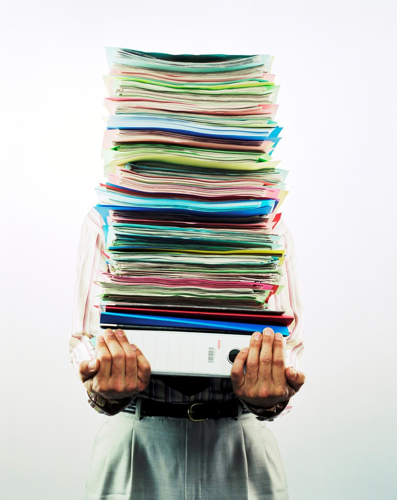 A person holding a stack of papers and files